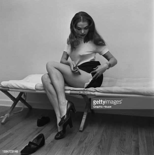Young woman sits on a camp bed hitching up her skirt as she injects a syringe into her left thigh arm, location unspecified, 1953.