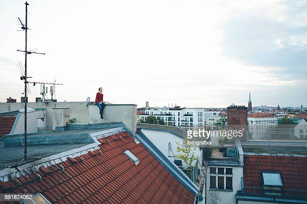 young woman sits on a roof and look far away - entfernt stock-fotos und bilder