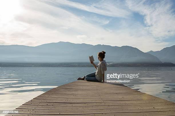 Junge Frau sitzt auf dem Pier über dem See, ein Buch zu lesen