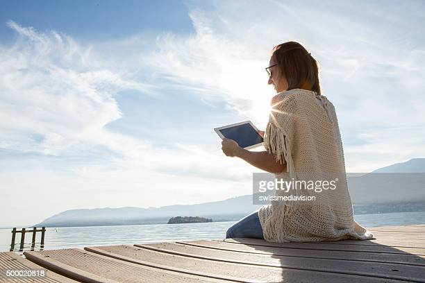 Young woman sits on jetty above lake, uses digital tablet