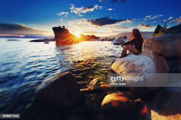 Young woman sits on Lake Tahoe shoreline by Bonsai Rock, watching sunset on summer evening