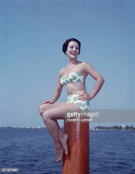 Young Woman Sits On Post At Beach