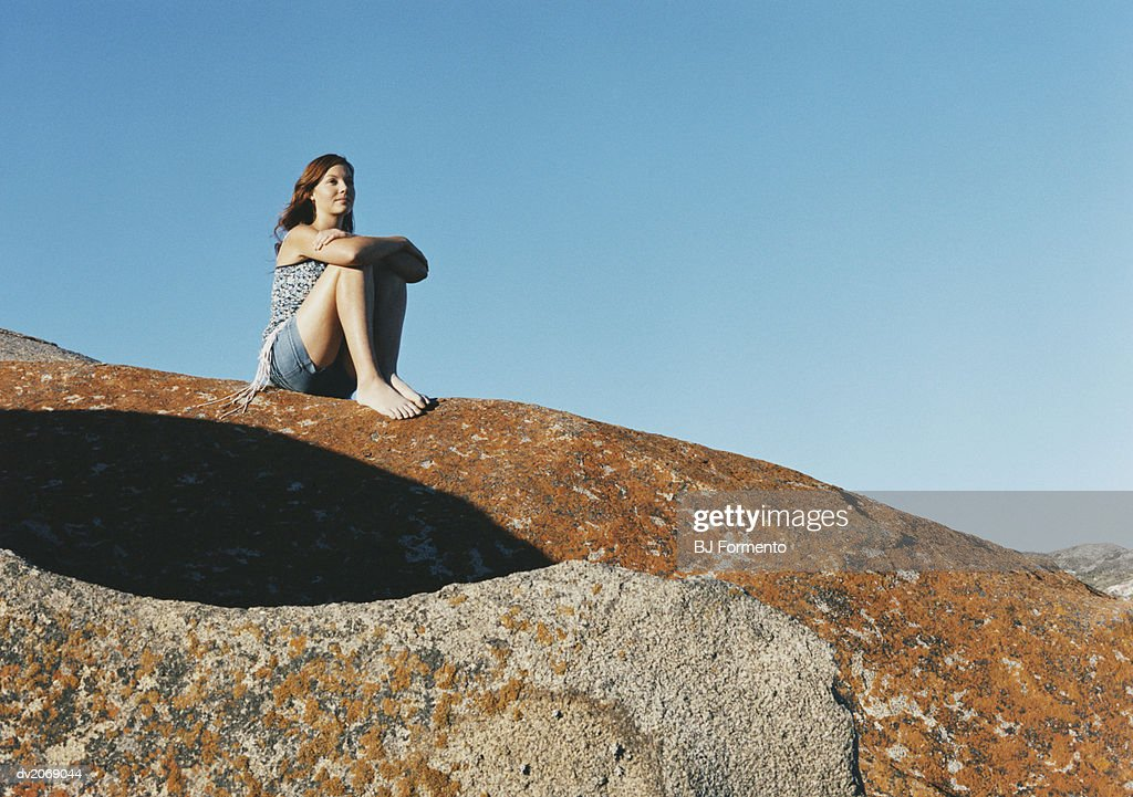 Young Woman Sits on Rock Looking at View : Stock Photo