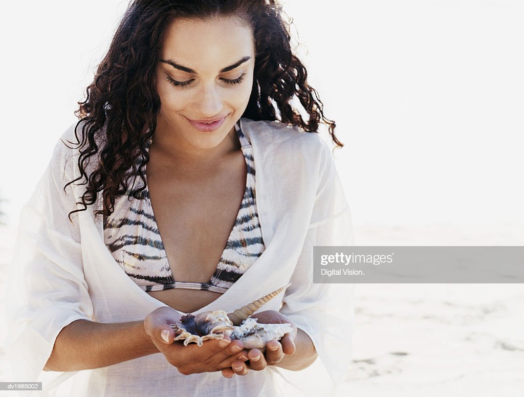 Young Woman Sits on the Beach Looking Down at Seashells She is Holding : Stock Photo