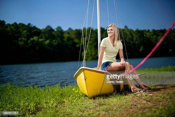 a young woman sits on the edge of a yellow sailboat. - pelham alabama stock pictures, royalty-free photos & images