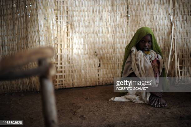 A young woman sits on the floor as she waits to receive medical help at the outpatient unit of a medical center run by Médecins Sans Frontières in...