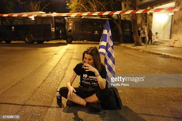 TURKEY ATHENS ATTICA GREECE A young woman sits on the ground in front of the police cordon holding a Greek flag Greeks from the Pontus region hold a...