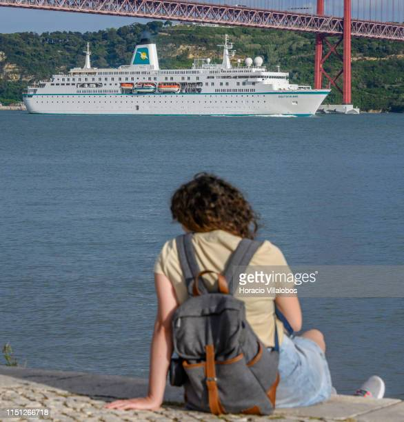 A young woman sits on the riverside while MS Deutschland a cruise ship registered in Nassau Bahamas sails the Tagus River towards the 25 de Abril...