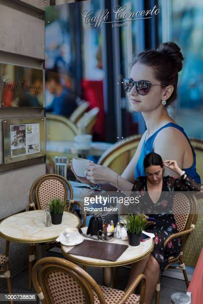 A young woman sits outside at Caffe Concerto a central London business on 13th July 2018 in London England