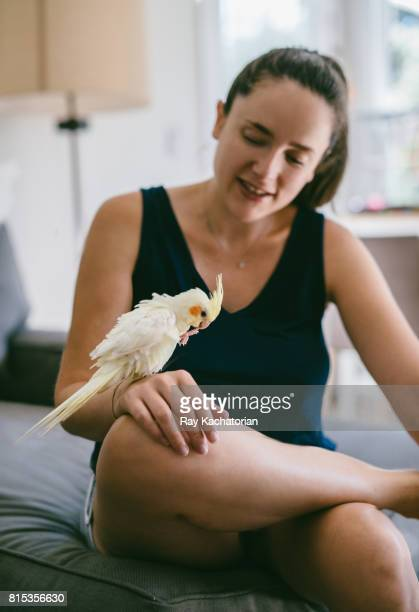 Young woman sits with cockatiel