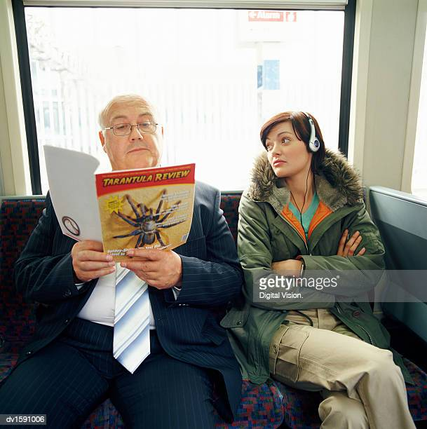 Young Woman Sits With her Arms Crossed Staring at an Overweight Businessman Sitting Next to Her Who is Reading a Magazine
