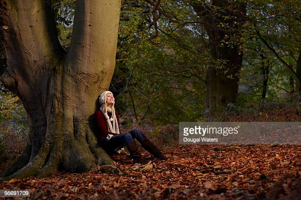 Young woman sitting against tree trunk.