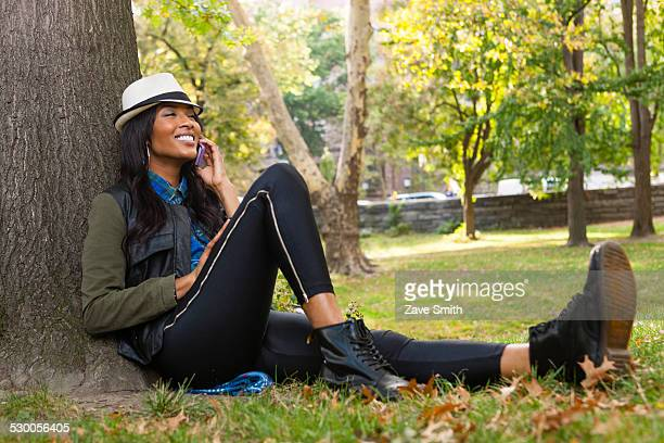 Young woman sitting against tree using smartphone