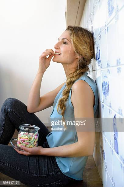 Young woman sitting against wall, eating sweets from jar