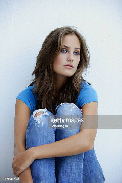 young woman sitting against wall, hugging knees - beautiful czech women stock photos and pictures