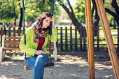 attractive brunette female sitting swings at