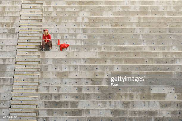 Young Woman Sitting Alone in Bleachers
