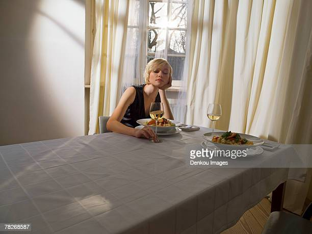 A young woman sitting alone on a table laid for two.