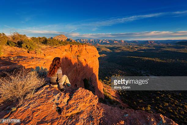 Young woman sitting alone on edge of cliffs of Doe Mountain overlooking Sedona Arizona valley at sunset