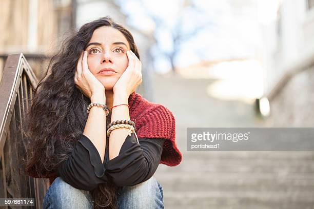 Young woman sitting alone on stairs