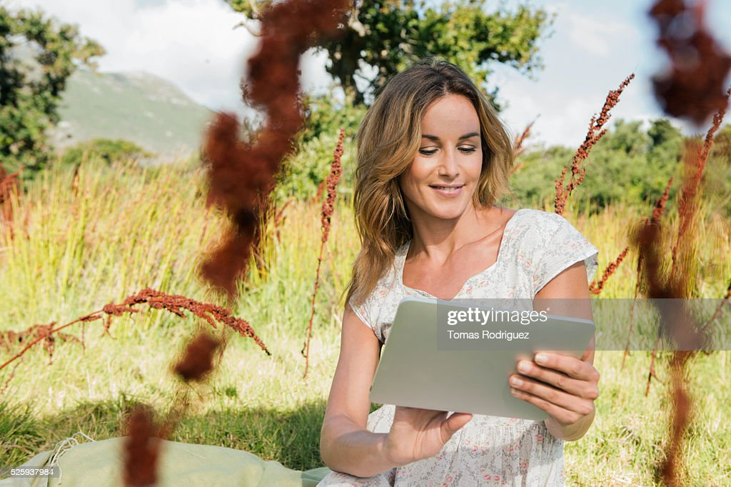 Young woman sitting among grass and using digital tablet : Stock Photo