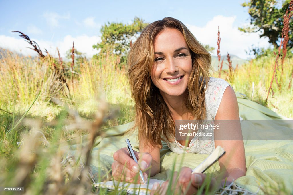 Young woman sitting among grass and writing in notebook : Stock Photo