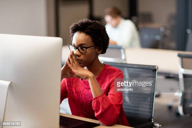 young woman sitting and looking at screen computer - in front of stock pictures, royalty-free photos & images