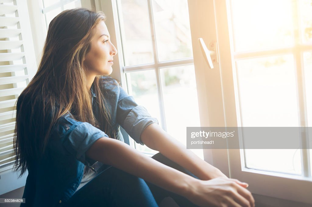 Young woman sitting and looking through window : Stock Photo