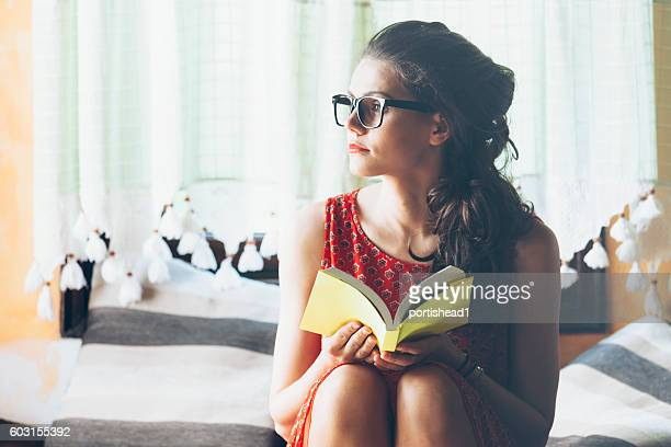 Young woman sitting and reading a book at home