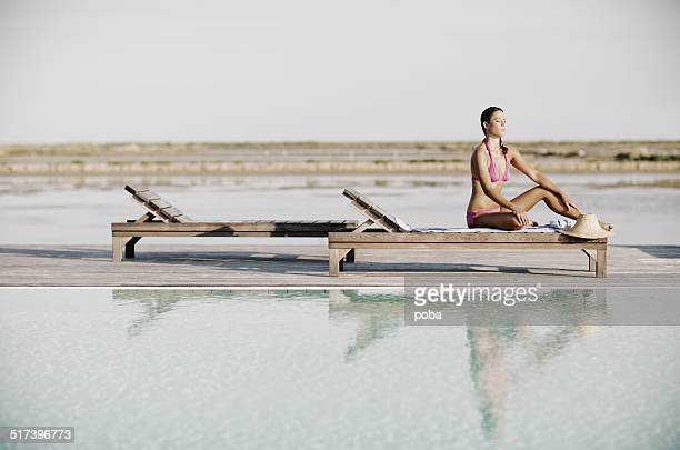 Joven mujer sentada y tomar el sol en la terraza de la piscina