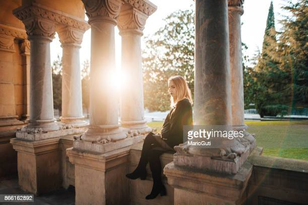 young woman sitting at a cloister - cloister stock pictures, royalty-free photos & images