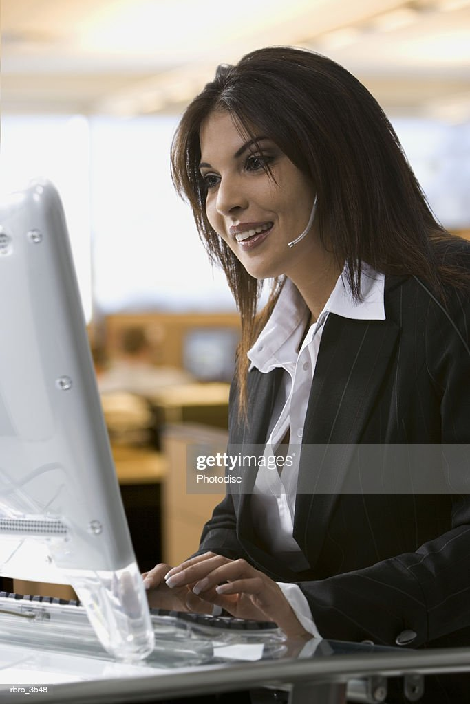 Young woman sitting at a desk using a computer : Foto de stock