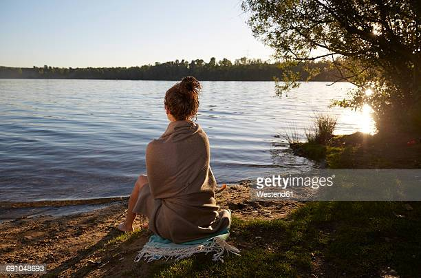 Young woman sitting at a lake at sunset