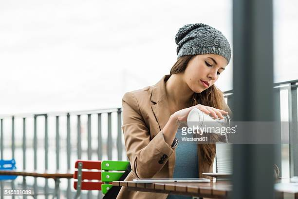 young woman sitting at a sidewalk cafe - sugar coffee stock photos and pictures