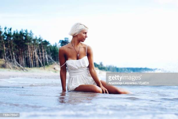 Young Woman Sitting At Beach Against Sky