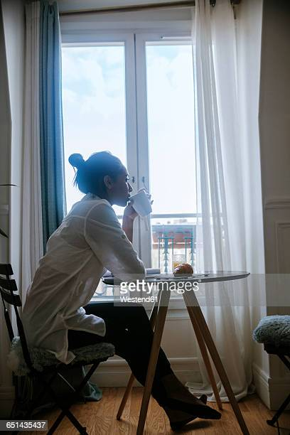 Young woman sitting at breakfast table drinking coffee