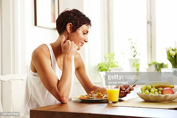 Young woman sitting at breakfast table holding mobile phone