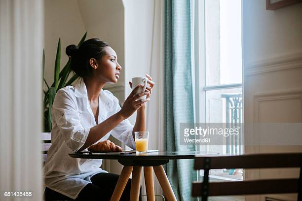 Young woman sitting at breakfast with cup of coffee looking through window