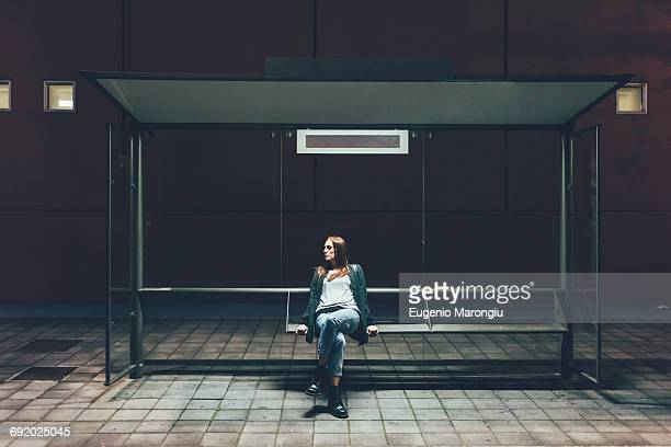 young woman sitting at bus stop at night - esperar - fotografias e filmes do acervo