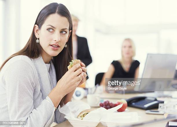 Young woman sitting at desk eating sandwich