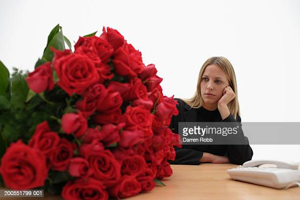Young woman sitting at desk looking at large bunch of red roses