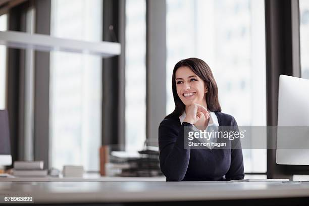 Young woman sitting at desk looking away in office