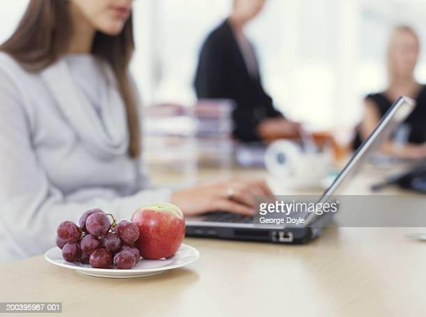 Young woman sitting at desk using laptop with grapes and apple