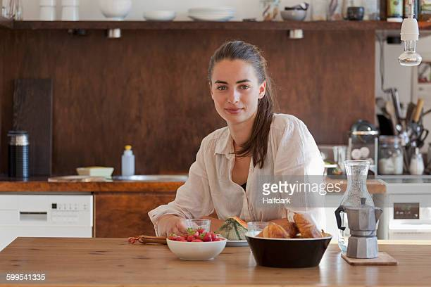 Young woman sitting at dining table, portrait