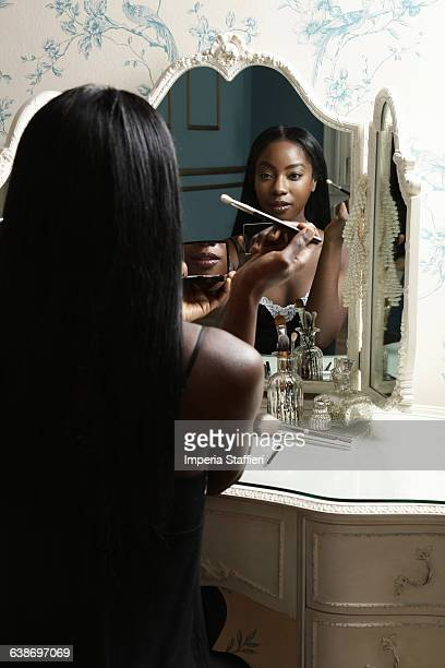 Young woman sitting at dressing table, applying make-up