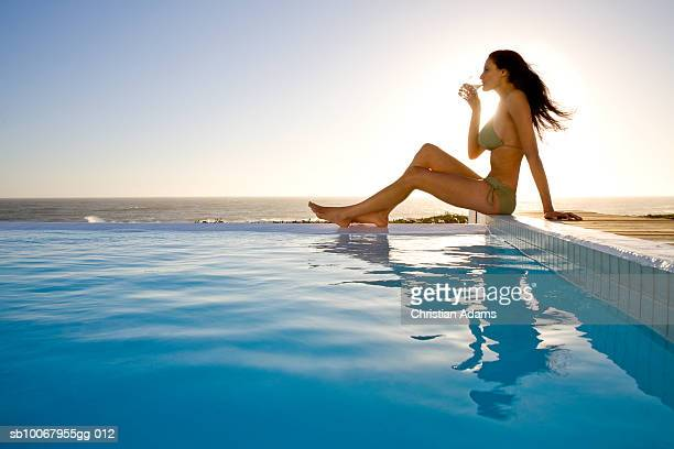 Young woman sitting at edge of swimming pool, drinking water, side view
