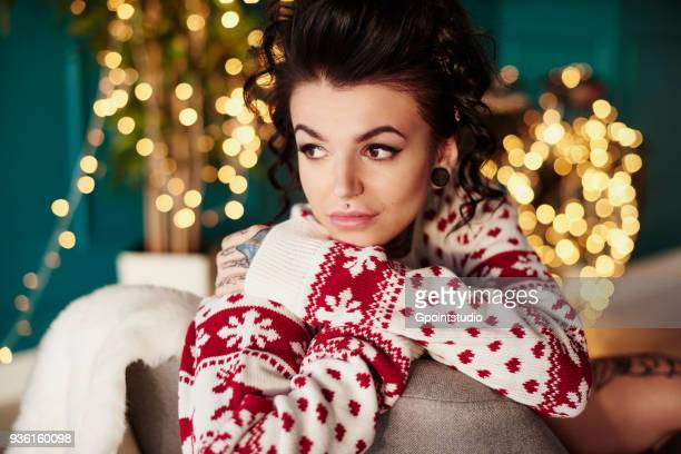 young woman sitting at home, wearing christmas jumper, thoughtful expression - christmas jumper fotografías e imágenes de stock