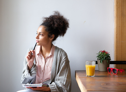Young woman sitting at home with pen and paper 525737425