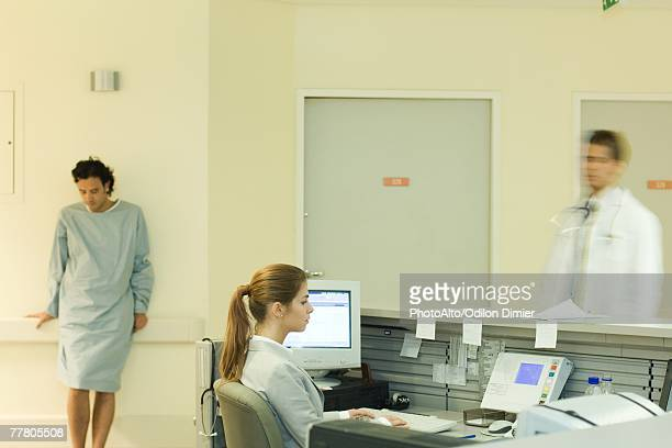 Young woman sitting at nurse's station, doctor and patient standing in background
