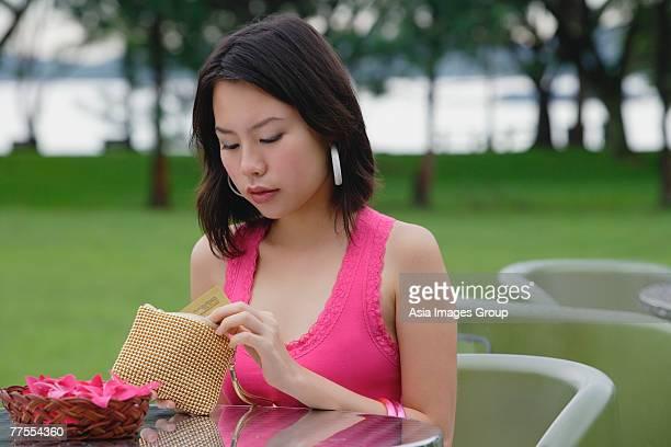 young woman sitting at outdoor table, looking into wallet - bolsa rosa - fotografias e filmes do acervo